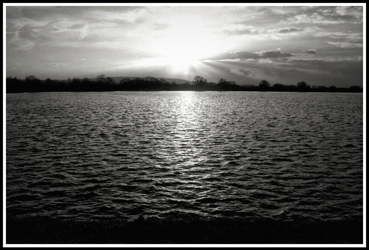 A heavy contrasted black and white image of the sun going down over a large lake