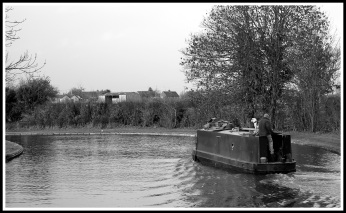 A black and white photo of a canal boat flowing from right to left
