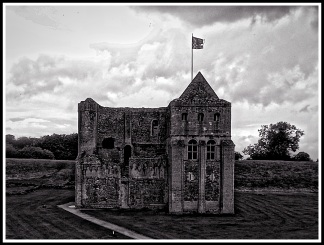 A dramatic black and white photo of castle rising castle in it's beautiful surroundings.