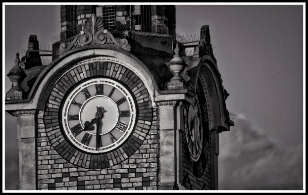 A close up black and white photo of the clock at the top of the tower