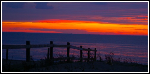 A beautiful sunset on Snettisham beach with a fence flowing down the beach from left to right