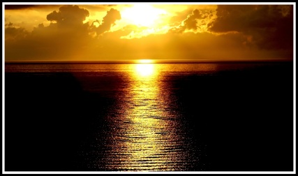 An centred orange sunset streaming beautiful bright light across the waves towards me