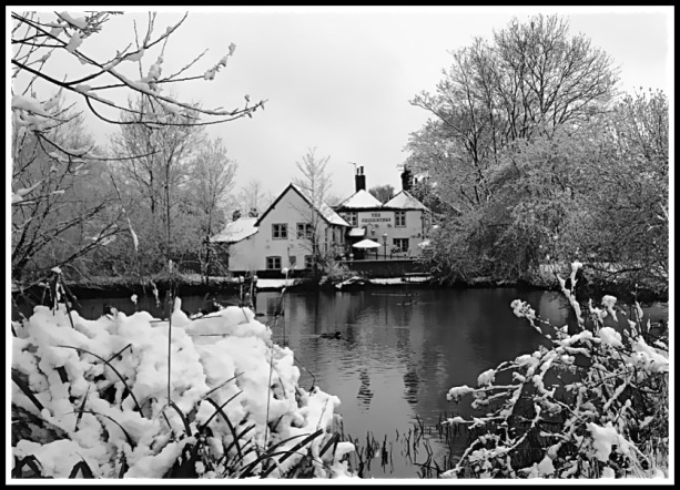 Photo of the Cricketers tavern in winter covered in snow with a stew pond in front