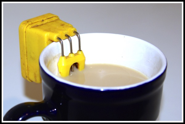 a liquid level indicator attached to the side of a blue cup filled up with tea