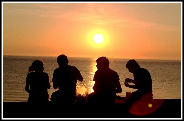 4 people sat on the beach wall with a beautiful sunset around them