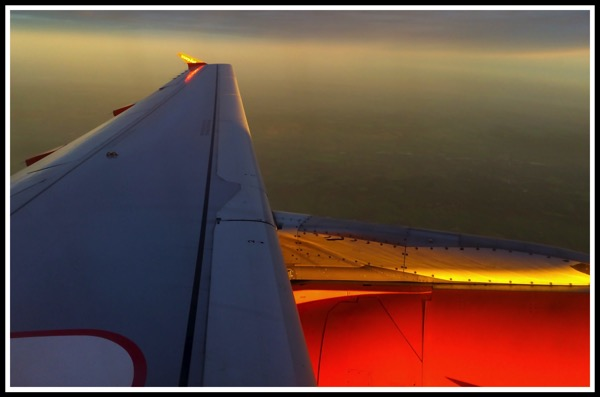 A photo looking out of the window onf the plane overlooking the wing and engine, with a beautiful coloured sunrise panarama!