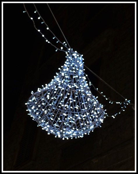 A blue light shaped as a bell hanging over the street
