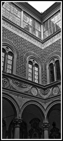 Black and white photo taken from the inner courtyard looking up to the roof of the Palazzo Medici Riccardi arches 2