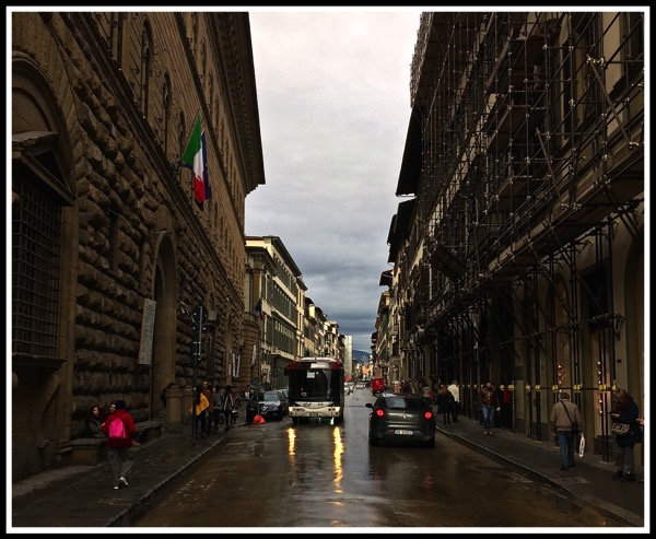 stood in the centre of the road with the palazzo medici riccardi on the left and a bus with its streaming light reflecting in the wet road