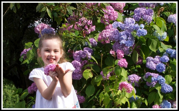 Ella smiling with a bunch of flower, stood next to a vividly coloured bush with lots of flowers