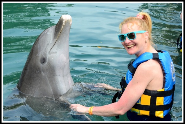 Sarah(on the right) in the water dancing with a Dolphin on her left