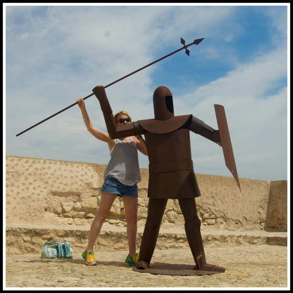 Sarah stood directly behind a warriour throwing a spear pretending to throw it too