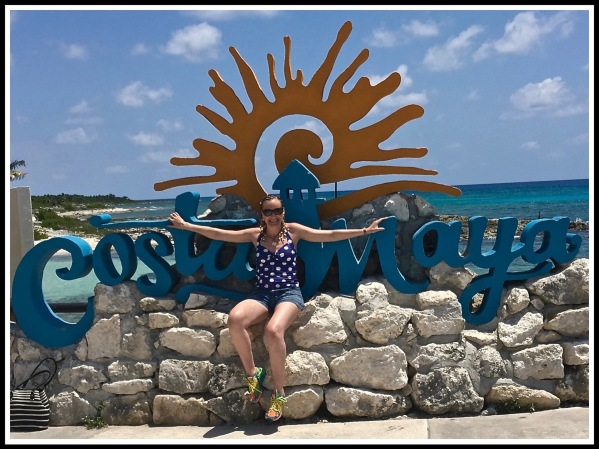 SARAH SAT IN FRONT OF A LARGE COSTA MAYA SIGN WITH THE LOVELY BLUE SEA IN THE BACKGROUND