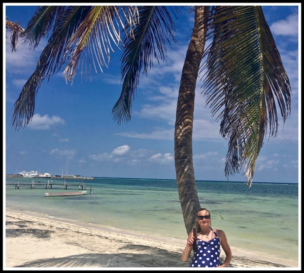 SARAH SAT AT THE BASE OF A BEAUTIFUL PALM TREE WITH THE AMAZING BLUE SEA AND YELLOW SAND LANDSCAPE BEHIND HER